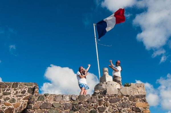 Les Fruits de Mer co-founders pose beneath a flag of the association's new logo at Fort Louis in Marigot.