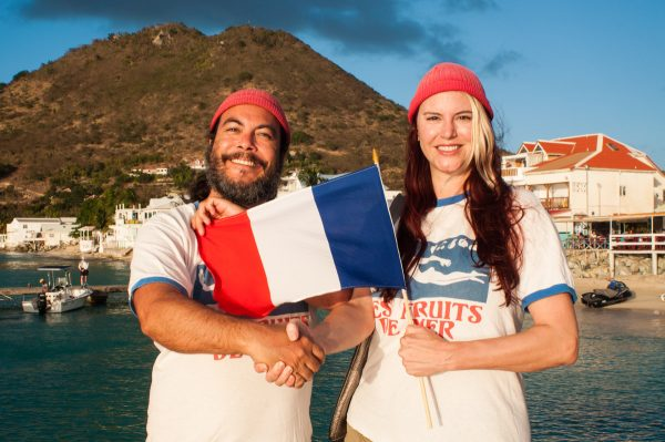 Les Fruits de Mer co-founders proudly display a flag with their new logo in Grand Case.